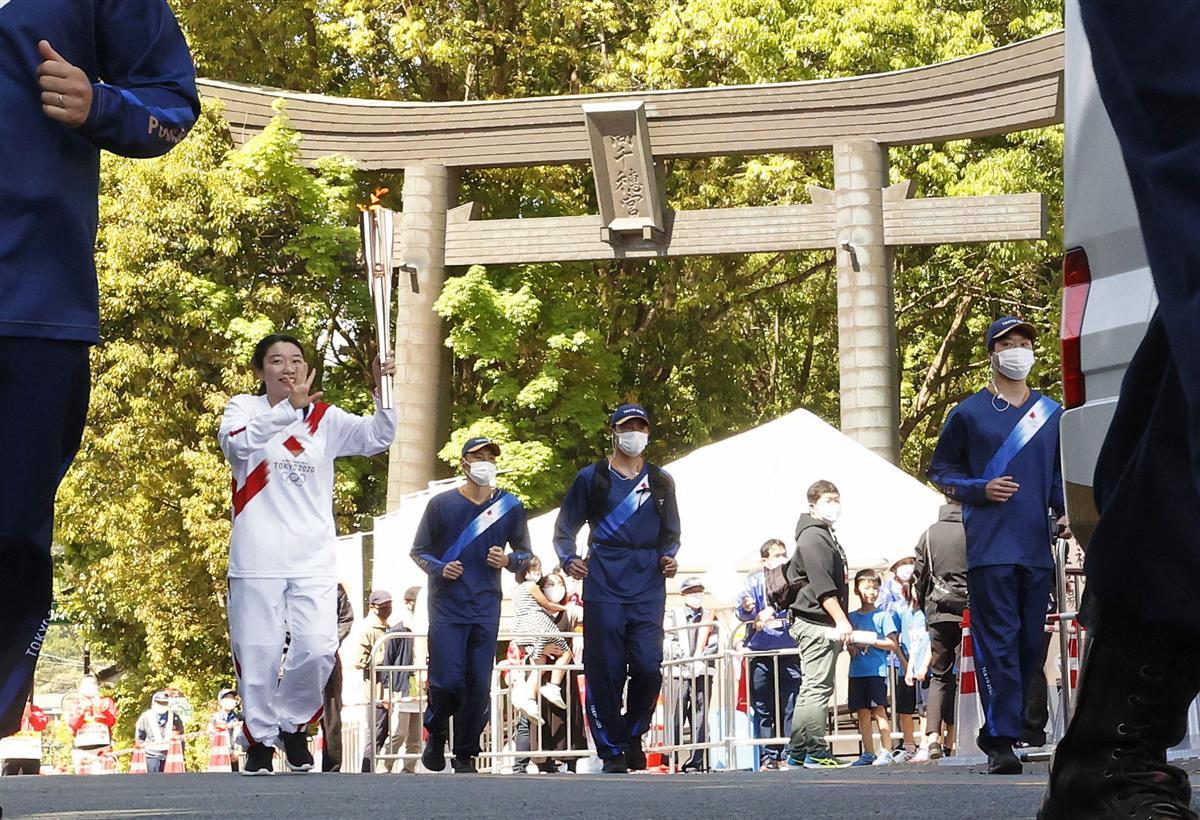 宮崎県高千穂町の高千穂神社を出発する聖火ランナーの後藤清香さん=25日午前