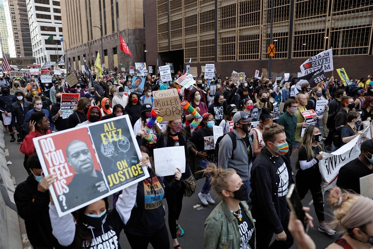 29日、米中西部ミネソタ州の地裁で始まったで黒人男性の死亡事件をめぐる本格的審理に合わせ、警察を批判してデモ行進する市民ら=ミネアポリス(ロイター)