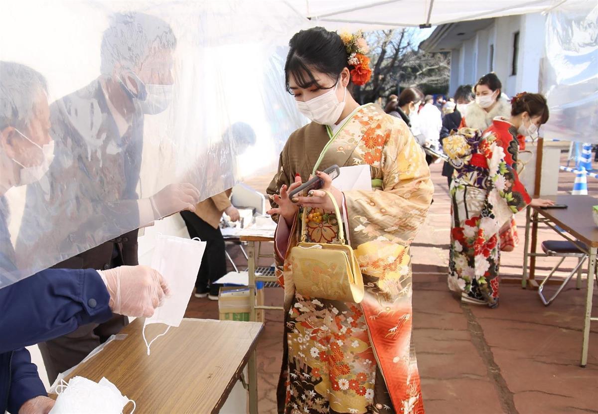 間隔を空けながら抗原検査の陰性結果を受付で提示する新成人たち。不織布マスクも配られていた=10日午後、茨城県つくばみらい市(永井大輔撮影)
