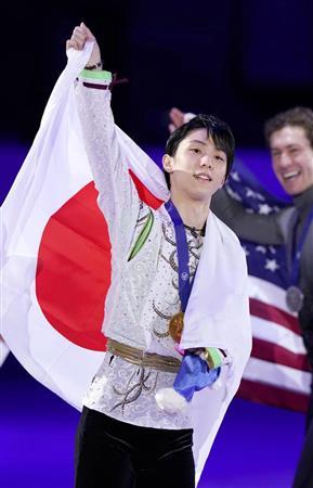 初優勝を果たし、日の丸を背に歓声に応える羽生結弦 右は2位のジェーソン・ブラウン=ソウル(共同)