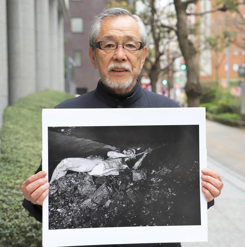 自身が昭和36年に福岡県で撮影した炭坑内の男性の写真パネルを手にする写真家の斎藤康一氏=東京都新宿区(奥原慎平撮影)