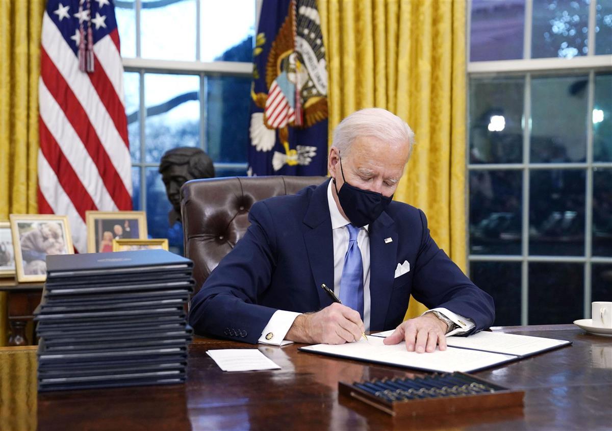 米ホワイトハウスの執務室で大統領令に署名するバイデン大統領=20日、ワシントン(AP)