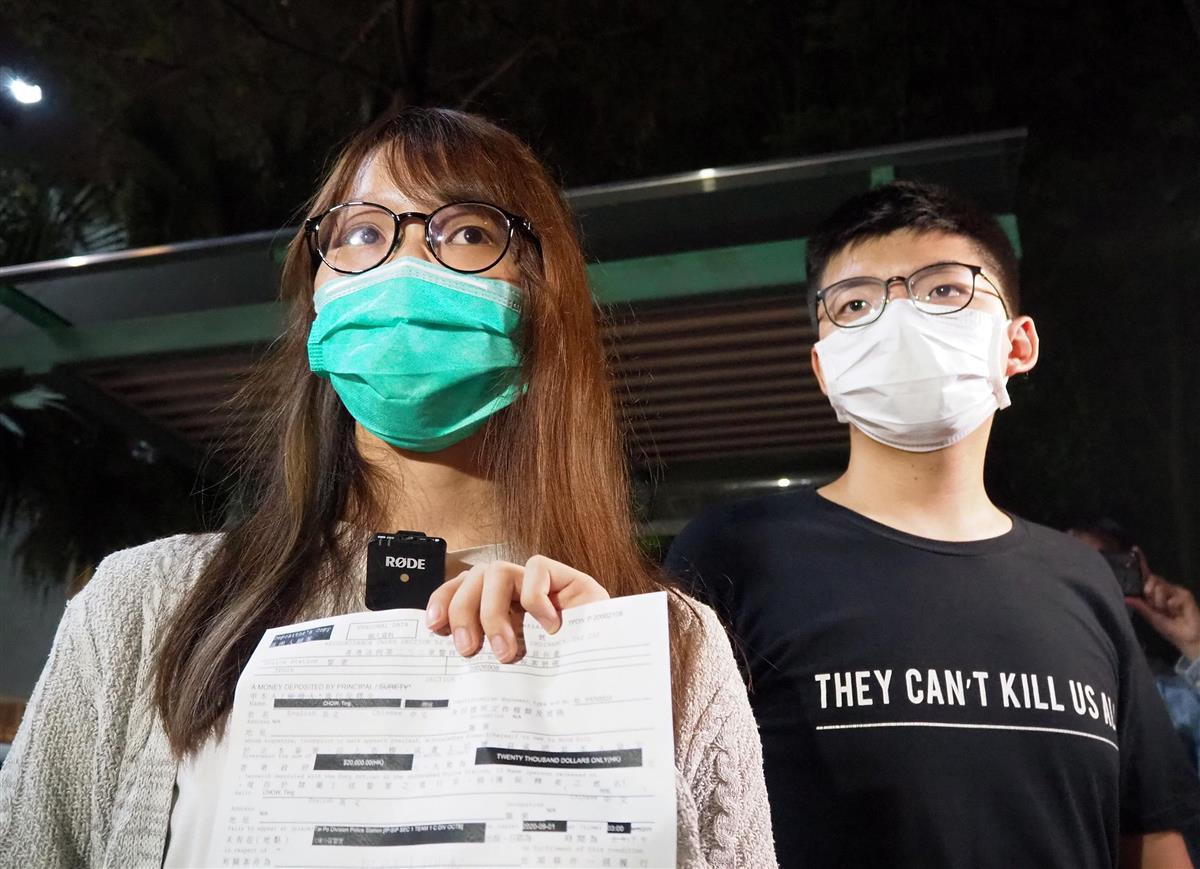 2020年8月11日、保釈後に香港の警察署前で会見する周庭氏(左)と付きそう黄之鋒氏(藤本欣也撮影)