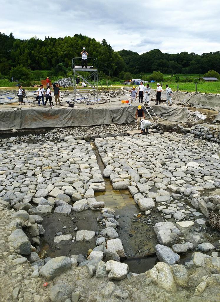 飛鳥京跡苑池北池で見つかった流水施設。手前に遊水池があり、奥(西)に流路がのびる。周囲は石敷き=明日香村