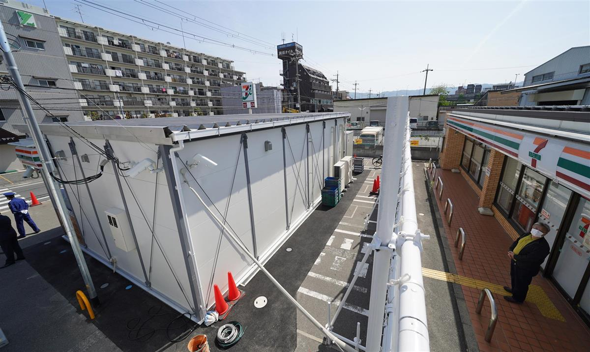 セブン-イレブン東大阪南上小阪店の駐車場にオープンした仮店舗(左)。元オーナー、松本実敏さんが壁を見上げていた=4日午前、大阪府東大阪市(沢野貴信撮影)