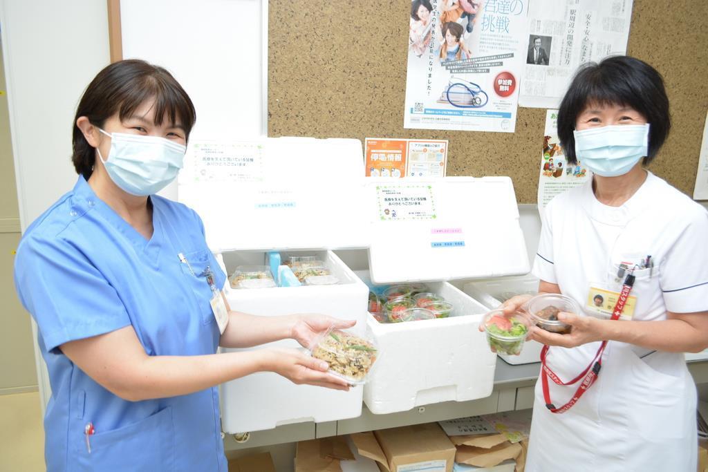 野菜を使った料理の贈り物を受け取る奈良県西和医療センター看護部長の春木邦恵さん(右)らスタッフ。「みんな、いつも楽しみにしている」という=奈良県三郷町