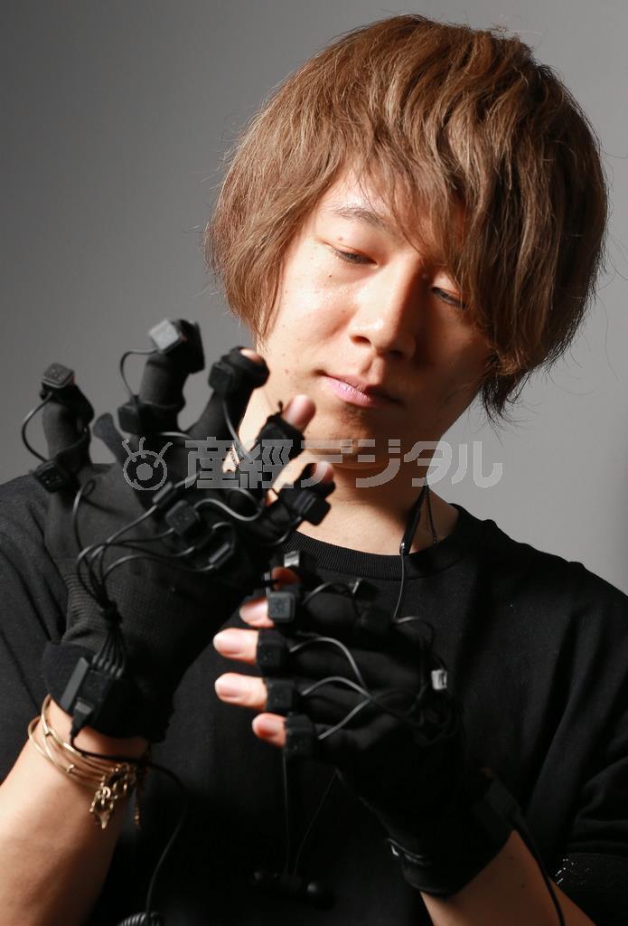手の加速度を測って動きを把握するグローブを身につける佐久間さん =大阪市北区(渡辺恭晃撮影)