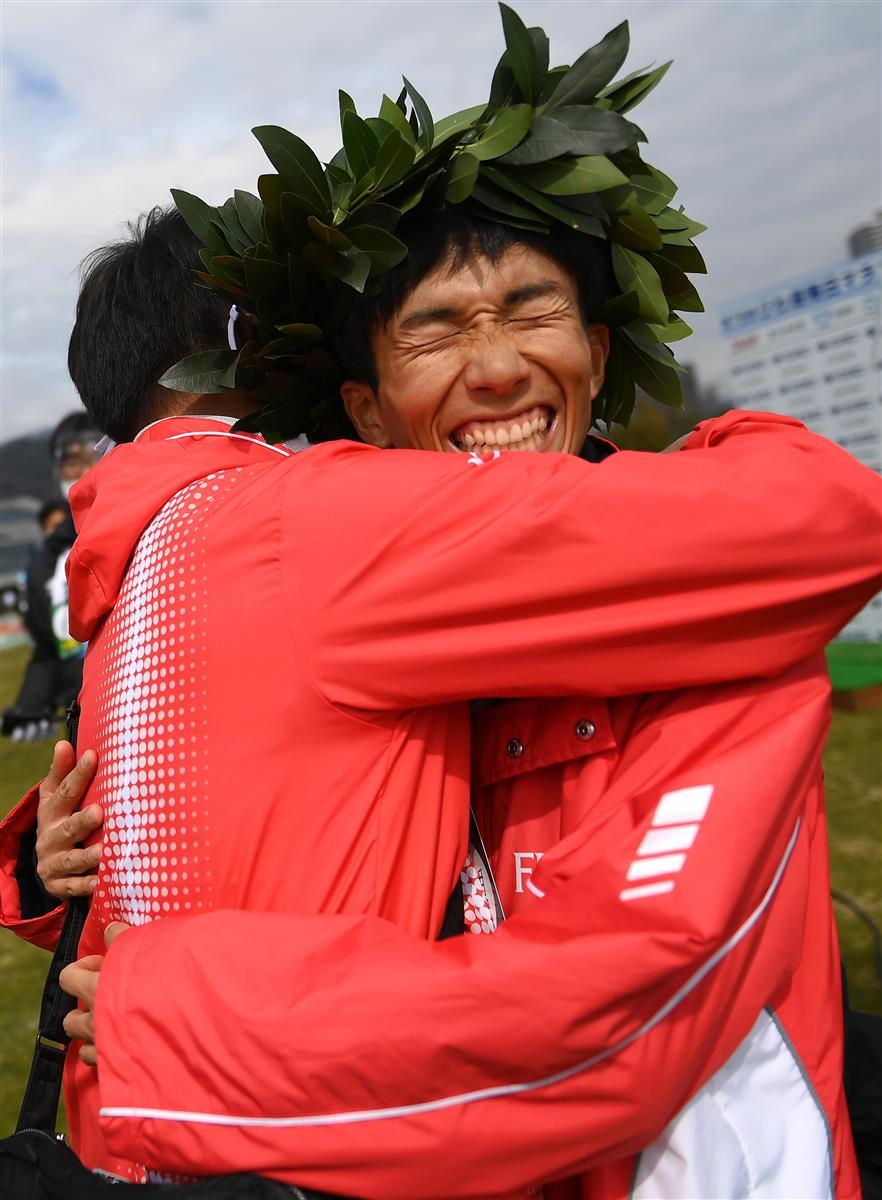 日本新記録で優勝し、関係者と抱き合って喜ぶ鈴木健吾=28日、大津市の皇子山陸上競技場(代表撮影)