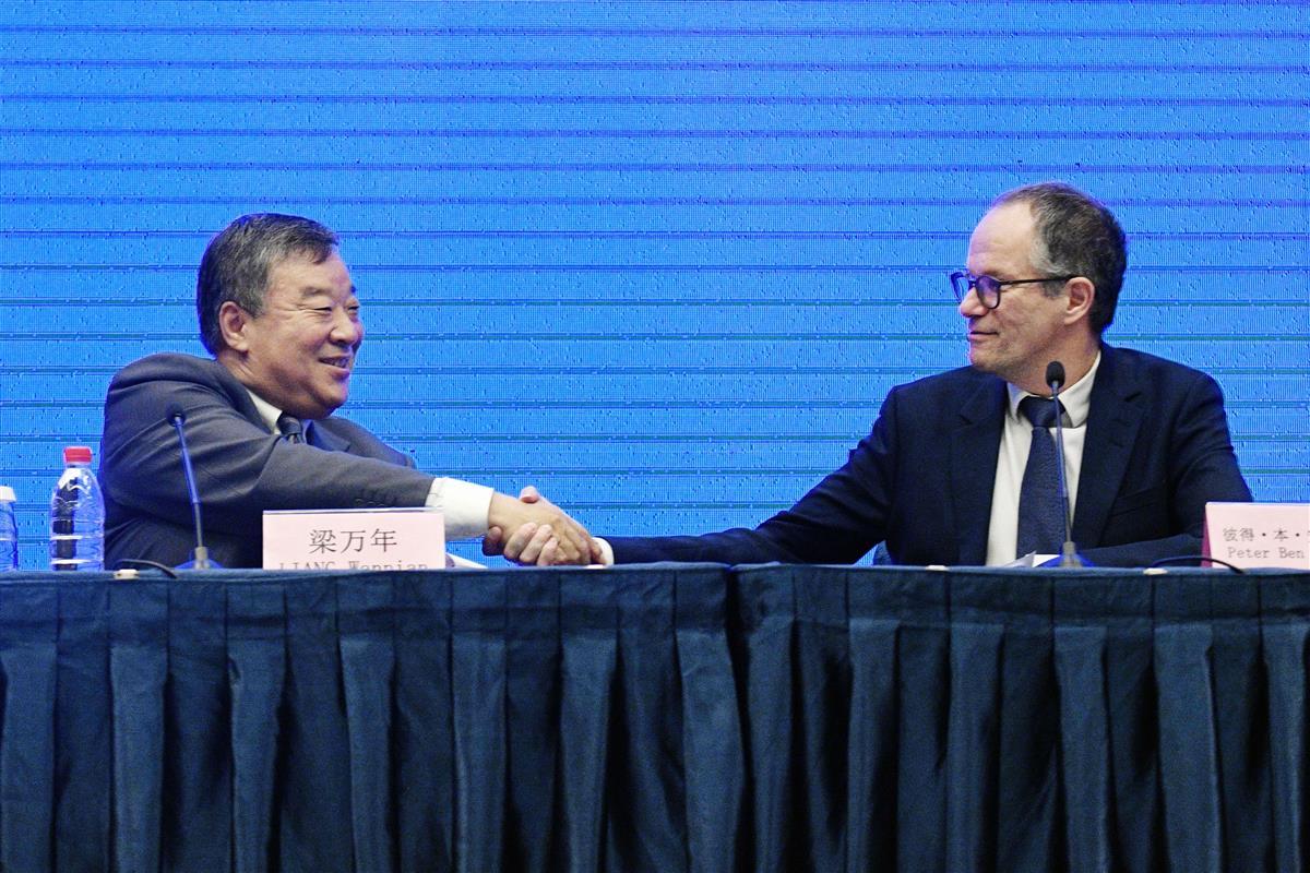 中国側の担当者(左)と握手するWHOの国際調査団のベネンバレク氏=9日、中国・武漢(共同)