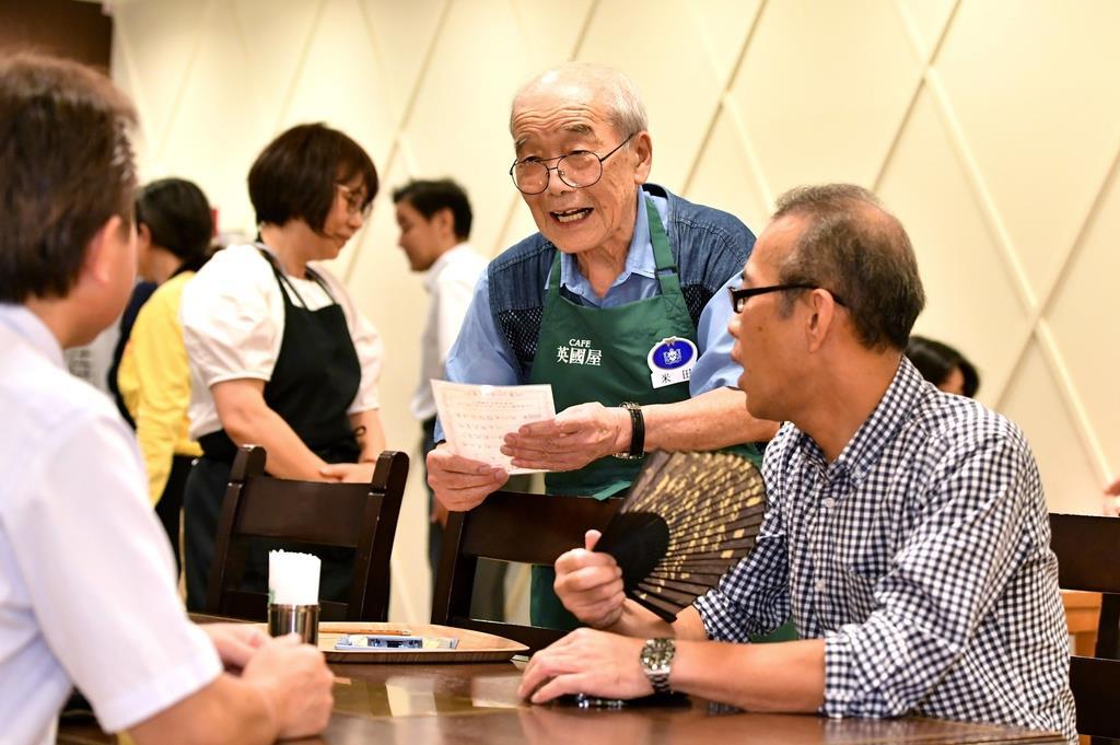 大阪市役所内の喫茶店で、緑のエプロン姿で接客する認知症の当事者=大阪市北区(南雲都撮影)