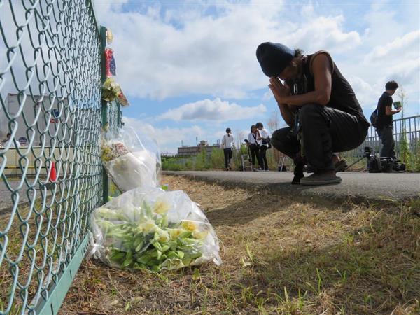 平田奈津美さんの遺体が見つかった現場で手を合わせる男性=13日午前、大阪府高槻市