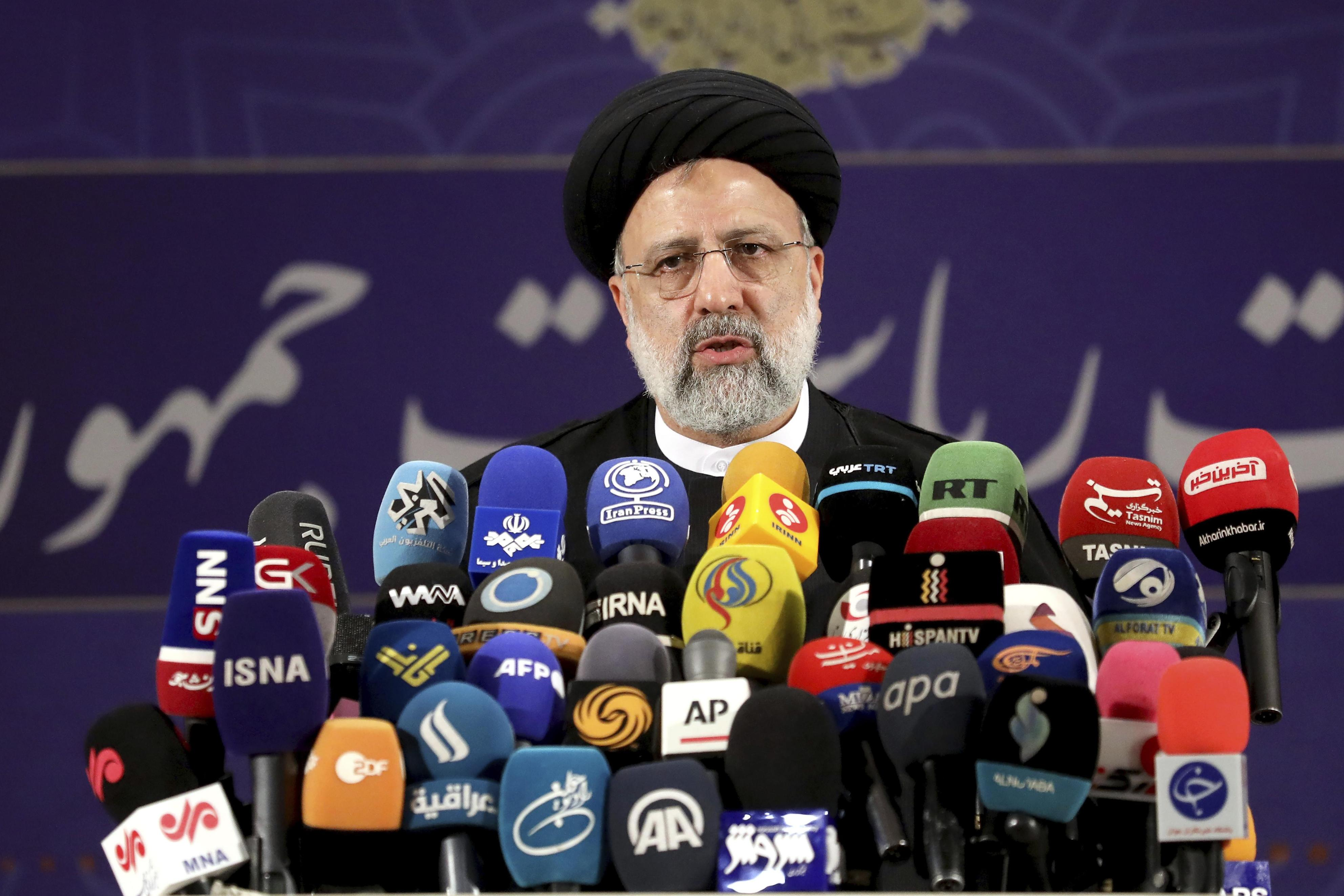 5月15日、テヘランでイラン大統領選への立候補を届け出た後、報道陣の取材に応じるライシ司法府代表(AP=共同)