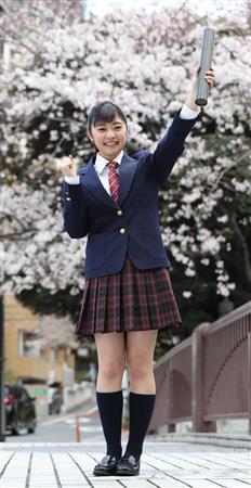 満開の桜をバックに卒業証書の筒を掲げ、とびきりの笑顔を見せる吉柳=東京・目黒区(撮影・大橋純人)