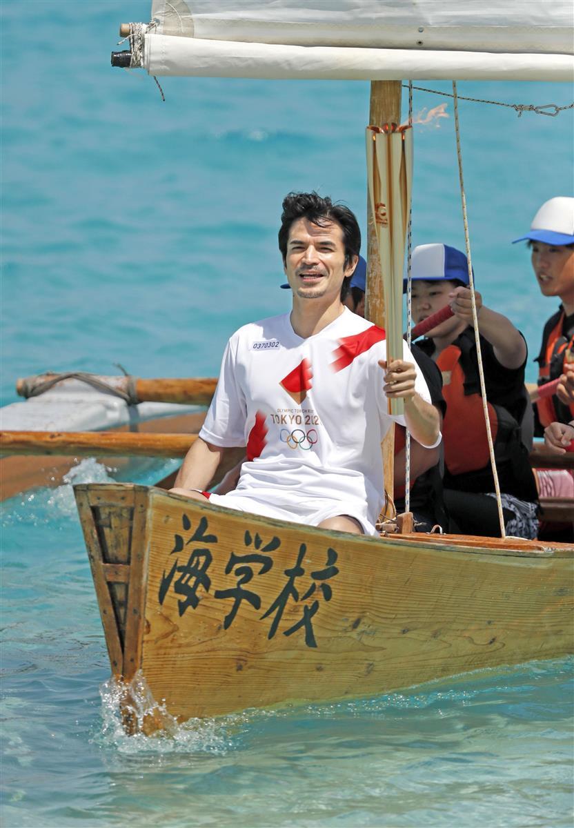 沖縄県座間味村の海上で、手こぎ舟「サバニ」に乗り込みトーチを掲げる尚玄さん=2日午後