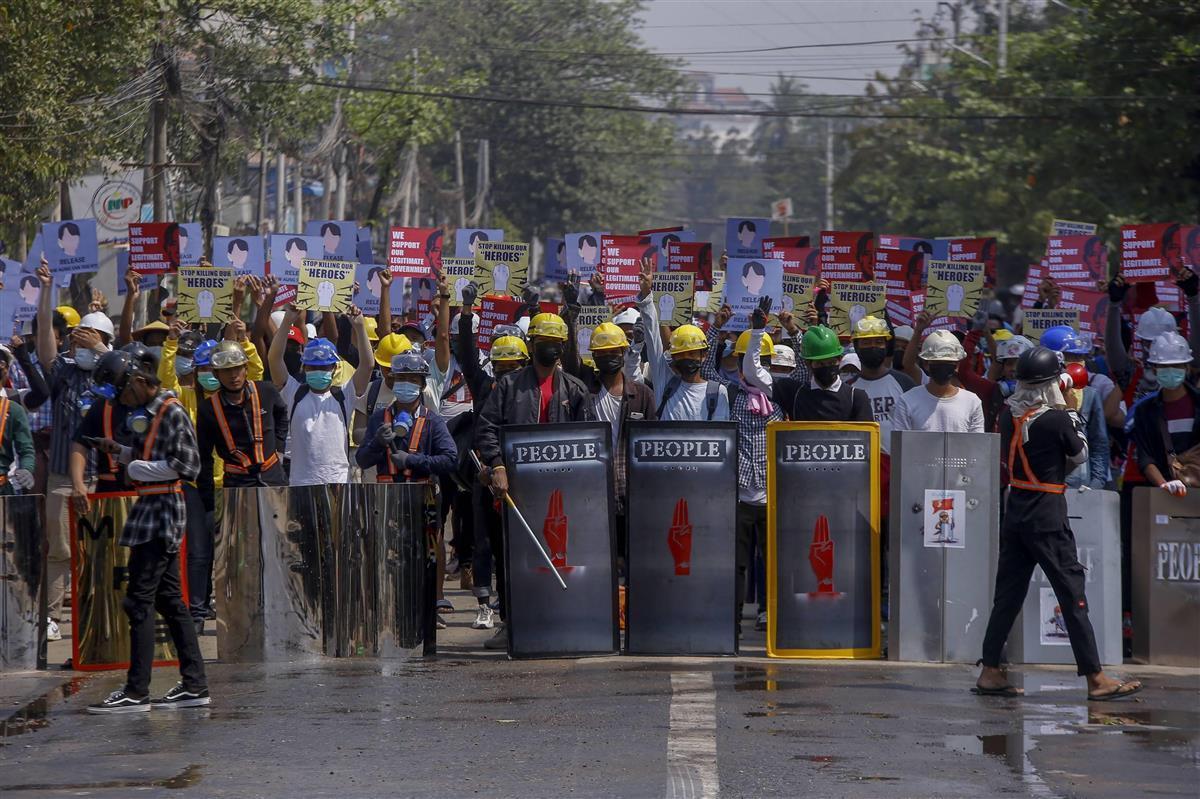 9日、ミャンマー最大都市ヤンゴンで、身を盾で守りながら国軍を非難するデモ隊(AP)