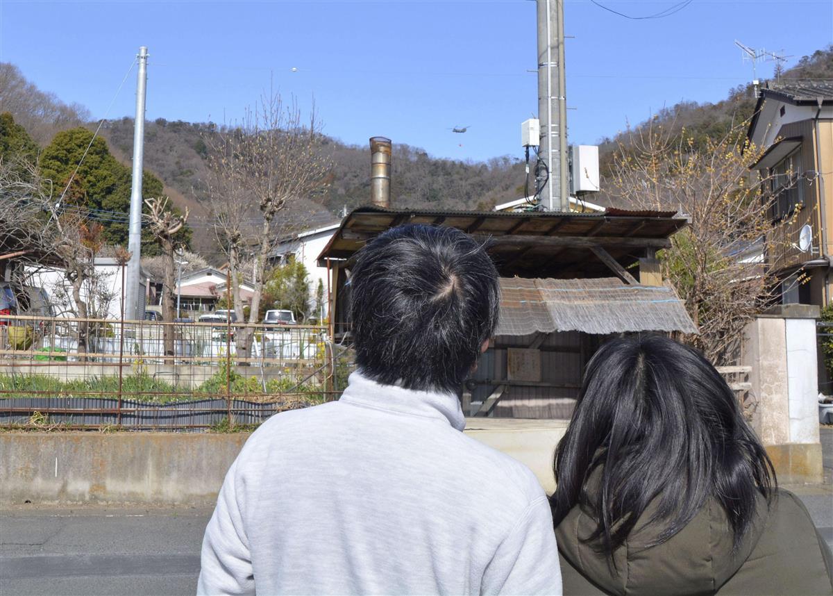 栃木県足利市の山林火災で、消火活動を見守る住民ら=27日午前9時49分