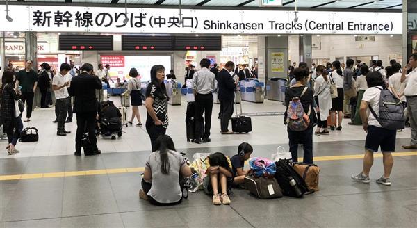 新大阪駅新幹線改札前で待ちくたびれる乗客ら=18日午前