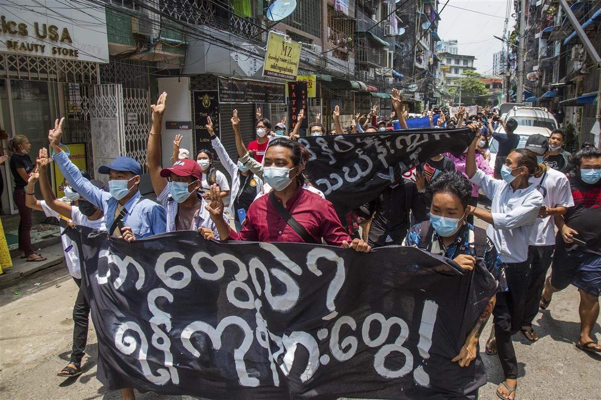 27日、ミャンマー・ヤンゴンで、国軍に抗議し横断幕を掲げながらデモ行進する市民ら(AP=共同)