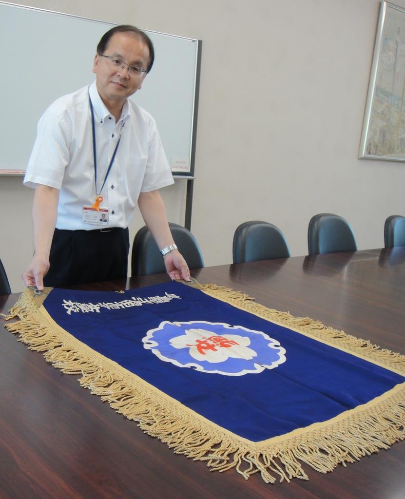 米国の図書館から返還された校旗と冨永六郎校長=7月25日、広島県海田町