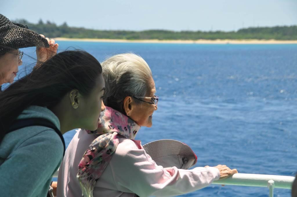 幼少期に生き別れた父の故郷、津堅島を見つめる冨里・ゼナイダ・スミコさん(右)=沖縄県うるま市(橋本昌宗撮影)