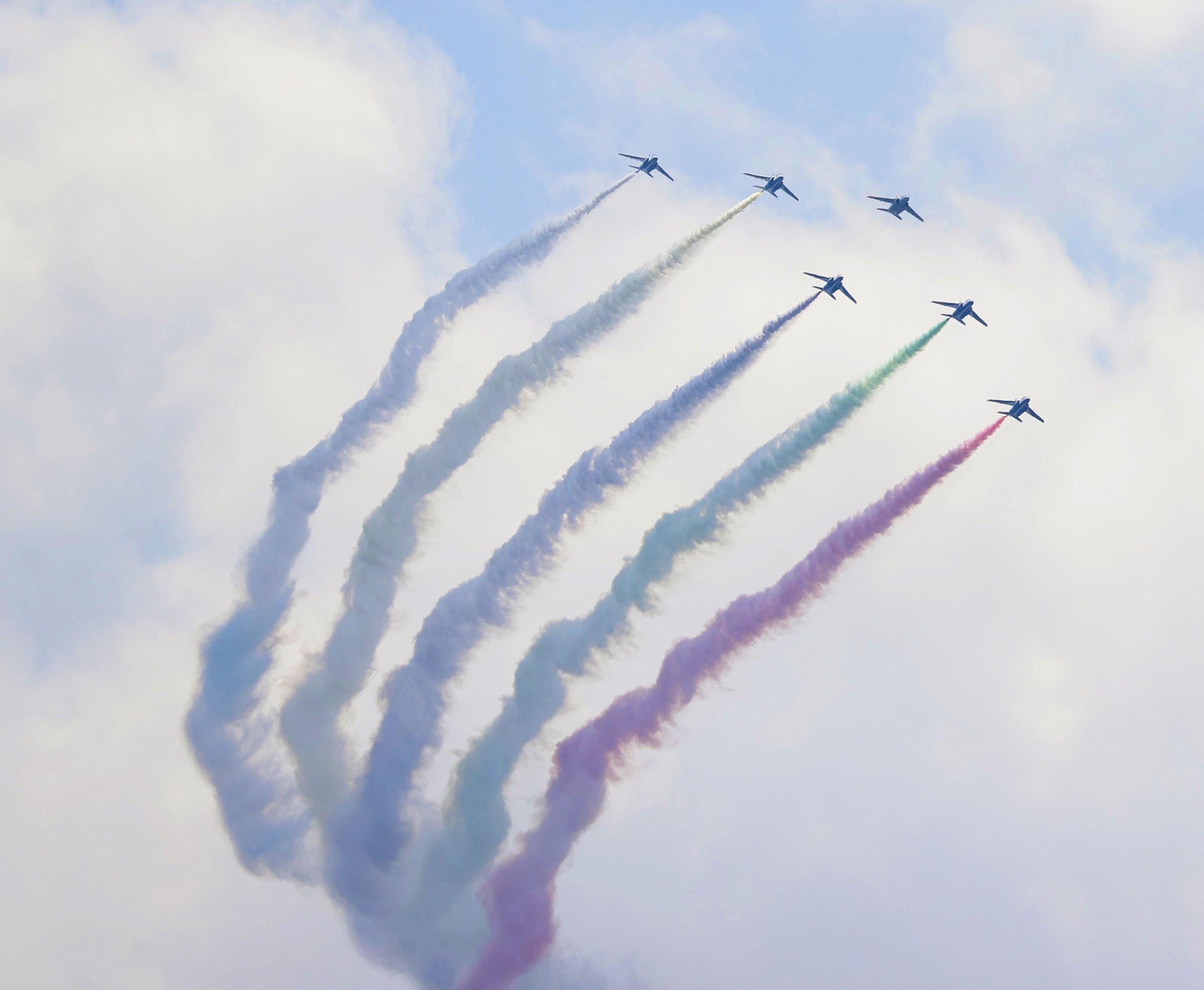 5色のカラースモークを出して都心上空を飛行する航空自衛隊の「ブルーインパルス」=23日午後0時42分、東京都港区