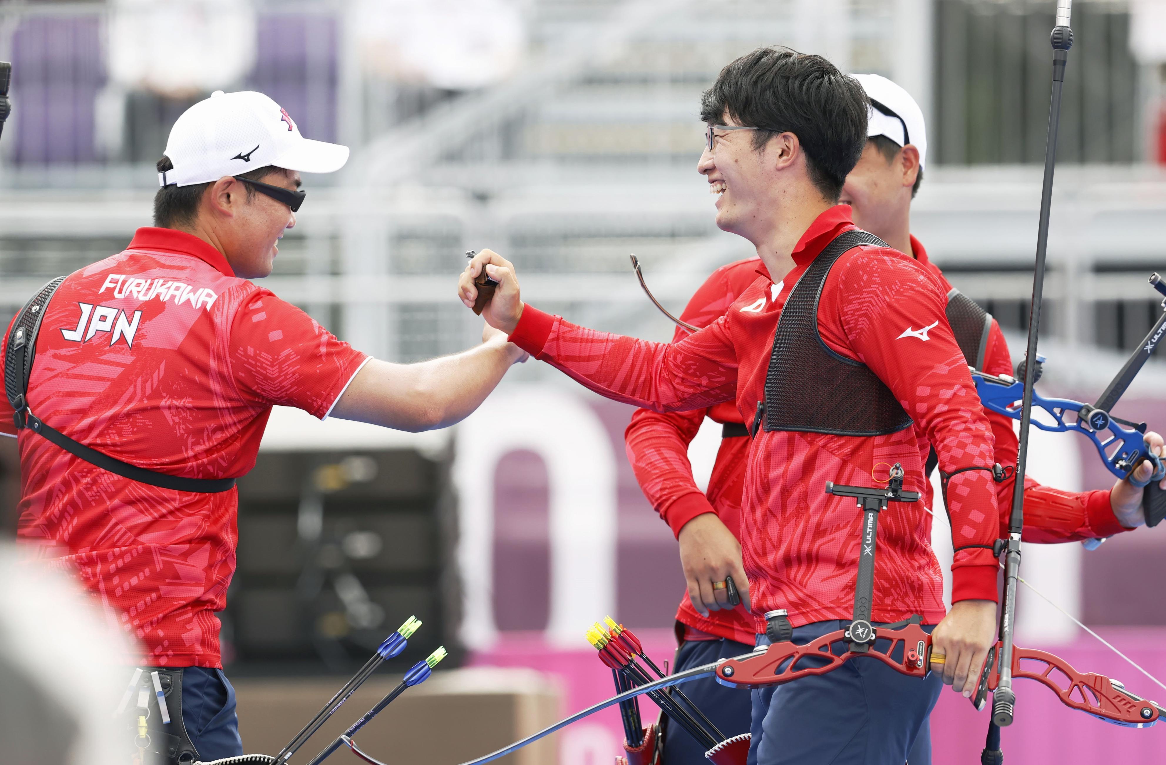 アーチェリー男子団体準々決勝で米国に勝ち喜ぶ古川高晴(左)と武藤弘樹=夢の島公園アーチェリー場