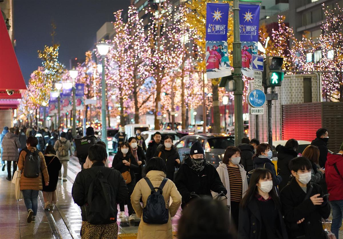 クリスマスイブを迎え、イルミネーションで彩られた御堂筋をマスク姿で行きかう人々=12月24日午後、大阪市中央区(恵守乾撮影)