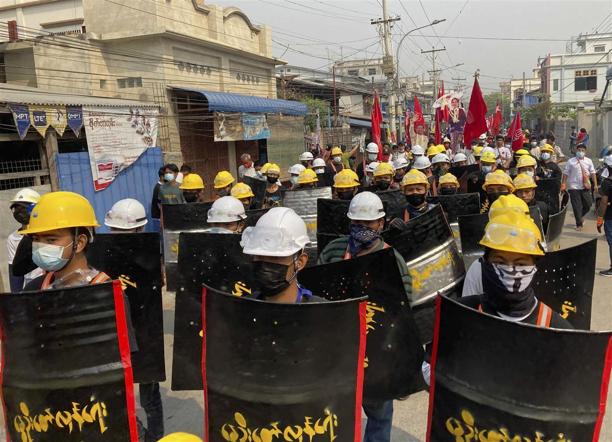 8日、ミャンマー第2の都市マンダレーで、簡易の盾を手に抗議する人々(AP)