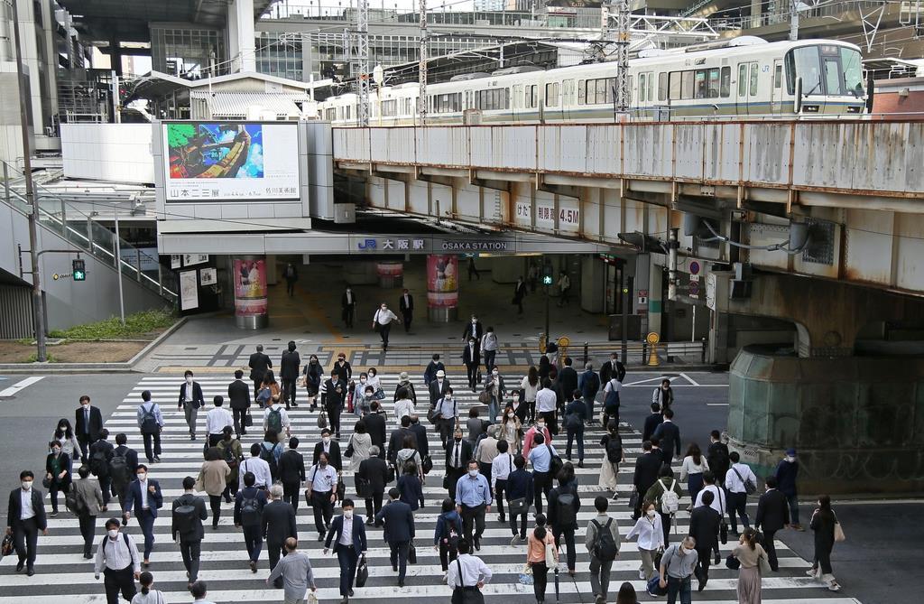 マスク姿で通勤する人たち=18日午前、大阪市北区のJR大阪駅前(彦野公太朗撮影)