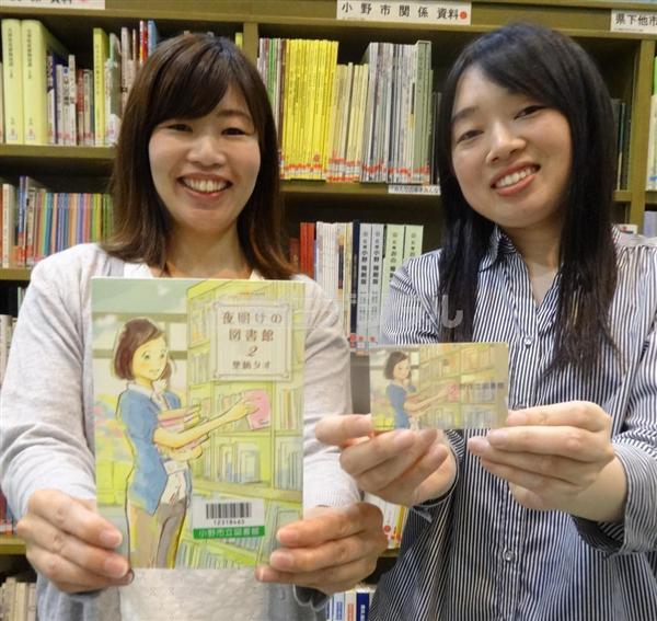 新しくなった図書館カード(右)と原画が表紙に使われている「夜明けの図書館」第2巻