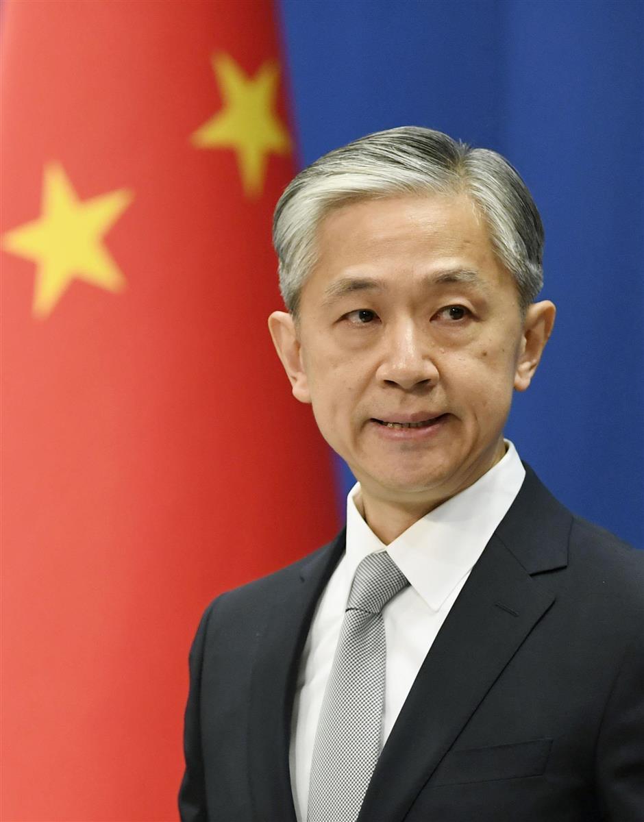 記者会見する中国外務省の汪文斌報道官=8日、北京(共同)