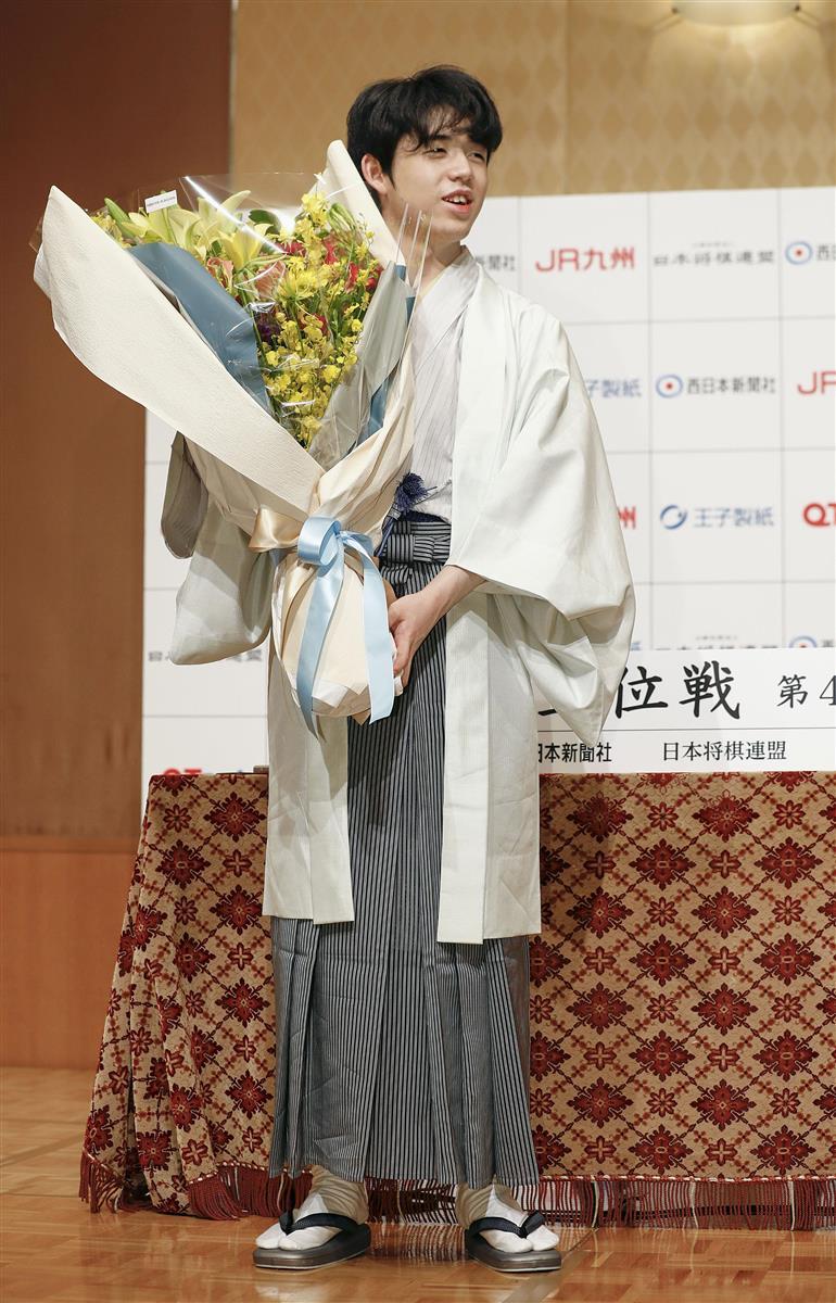 記者会見に臨む藤井二冠。花束を受け取ると笑顔をみせた=20日午後、福岡市中央区の西鉄グランドホテル