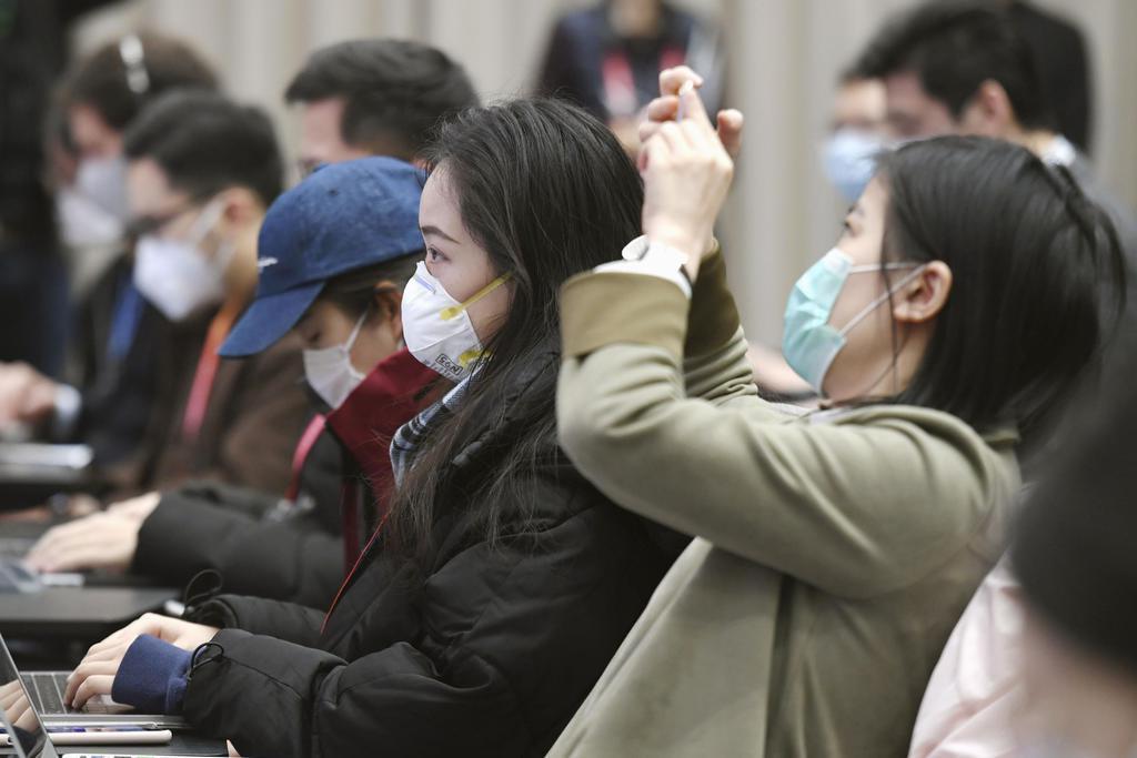 中国国家発展改革委員会の記者会見にマスクを着用して臨む記者ら=11日、北京(共同)